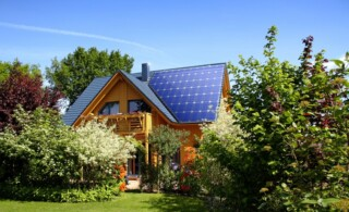 Home in a lush, green garden with a seamless, solar roof