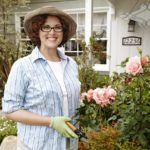 Smiling woman working in rose garden