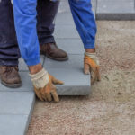 contractor lays pavers on patio
