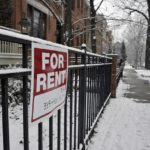 For rent sign on front fence of house in upscale urban neighborhood. The house is for rent during the depths of the winter season