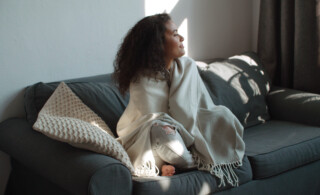 a woman wrapped in a blanket smiles on her couch